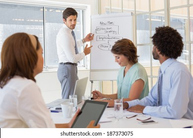 Portrait of a young businessman giving presentation to colleagues in a bright office