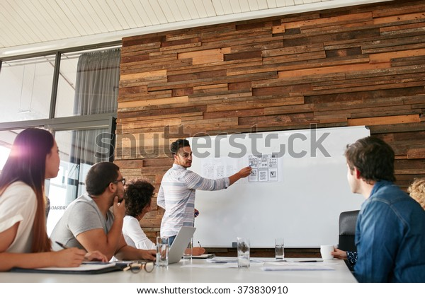 Portrait of young businessman giving presentation to colleagues. Young man showing new app design layout on white board to coworkers during business presentation.