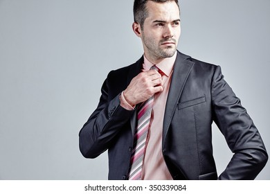 Portrait of young businessman with his hand at his tie isolated over grey