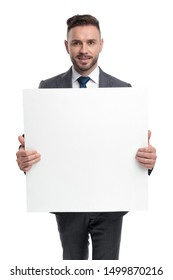 portrait of a young businessman holding a blank board on white background