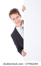 Portrait Of Young Businessman Holding Blank Placard Over White Background