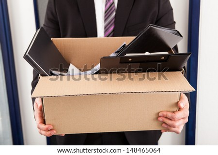 Portrait of young businessman holding cardboard in office