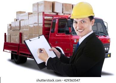 Portrait of a young businessman holding a clipboard with a logistic truck on the background
