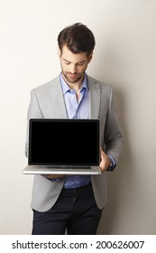 Portrait of young businessman holding laptop in his hand. Showing the screen. Small business.