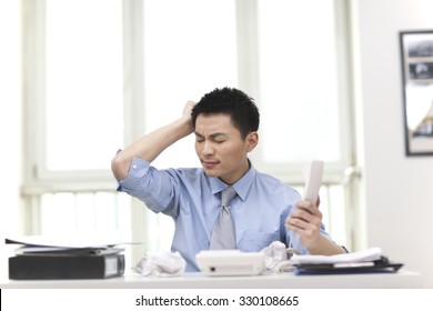 Portrait of young businessman holing phone in office