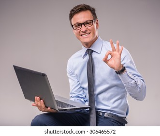 Portrait of a young businessman with a laptop on a gray background