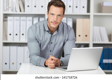 Portrait of a young businessman with laptop sitting at office desk
