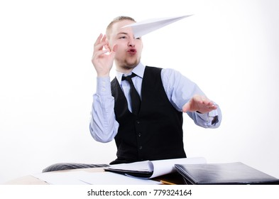 Portrait of young businessman launch a paper airplane at his workplace