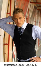 Portrait of young businessman leaning on a wall