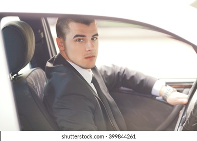 Portrait of a young businessman looking at camera while driving a car