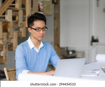 Portrait of young businessman in office with notebook