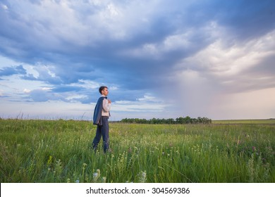 Portrait of young businessman on a green meadow
