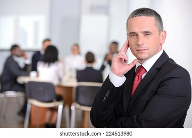 Portrait of a young businessman, people group in background at modern bright office indoors
