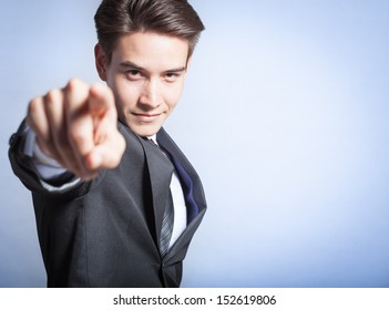 Portrait of young businessman pointing finger at viewer (isolated on blue background)