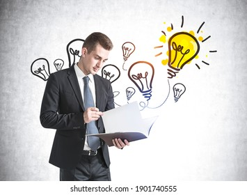 Portrait of young businessman reading document near concrete wall with colorful idea sketch drawn on it