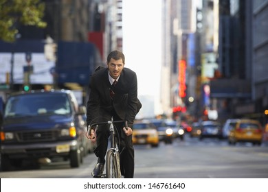 Portrait of young businessman riding bicycle to work on urban street