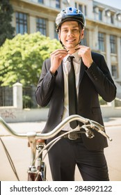 Portrait of young businessman riding bicycle to work on urban street.