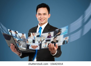 Portrait of young businessman sharing his photo and video files using laptop