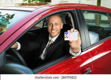 Portrait Of A Young Businessman Showing His Driving License From Open Car Window