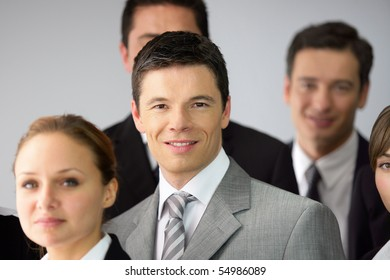 Portrait of a young businessman smiling among business people