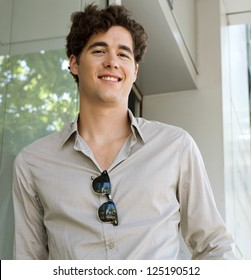 Portrait of a young businessman smiling at the camera while leaning on a modern office building, outdoors.