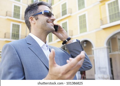 Portrait of a young businessman speaking on his cell phone in the financial district.