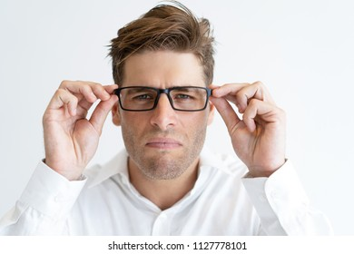 Portrait of young businessman squinting in new glasses. Caucasian male student trying on eyeglasses. Eyesight concept