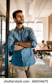 Portrait of young businessman standing at door while colleagues working in background. Young male at startup office.