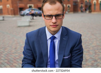 Portrait of young businessman standing in front of office block. Outdoor photo.