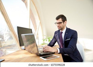 Portrait of young businessman in suit and glasses using laptop while sitting at office desk and working on new project.