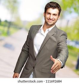 Portrait Of  Young Businessman In A Suit Holds Out His Hand For A Handshake, Outdoor