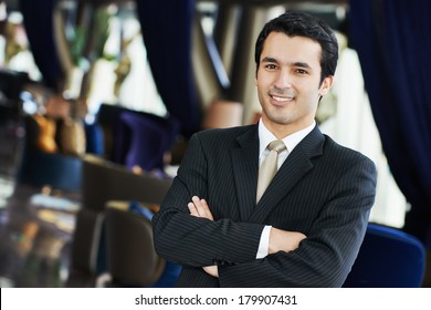 Portrait of a young businessman in suit standing at hotel interior