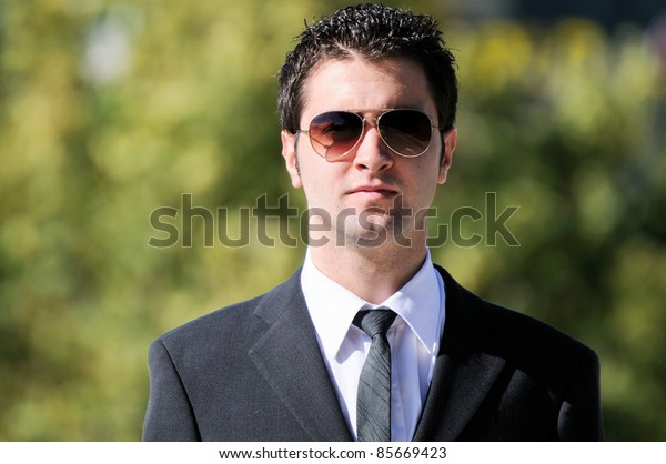 A portrait of a young businessman with sunglasses