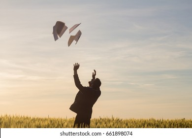 Portrait of young businessman throwing sheets of paper into the air, sunset in summer fields background