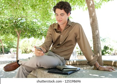 Portrait of a young businessman using his smart phone while sitting on a ben in a city park with a paperwork folder, outdoors.