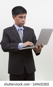 Portrait of  young businessman using laptop. Vertical shot. Isolated on white.