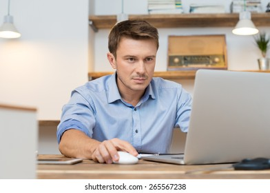 Portrait of young businessman using laptop in office