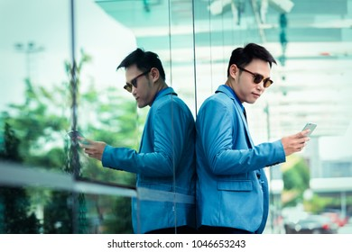 Portrait of a young businessman using on smartphone beside modern office, process color.