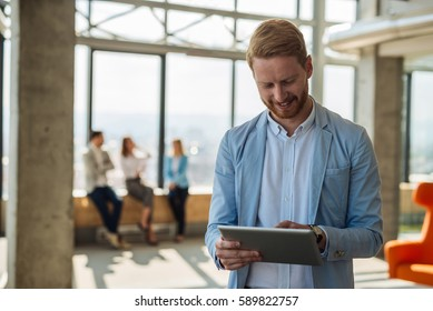 Portrait of a young businessman waiting for an interview and holding a digital tablet in the firm.
