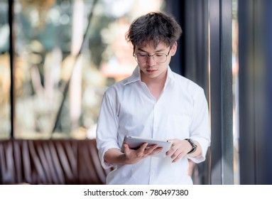 Portrait of young businessman wear glasses with digital tablet in office
