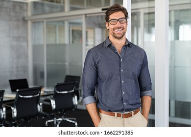 Portrait of young businessman wearing eyeglasses and standing outside conference room. Portrait of happy business man wearing spectacles and looking at camera with copy space. Satisfied proud man. - Shutterstock ID 1662291385