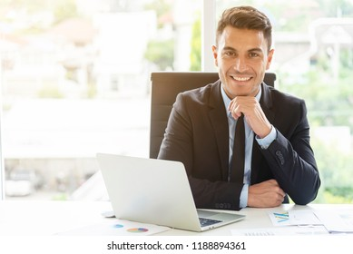 Portrait of young businessman working in office with smile. Manager or smart working people concept.