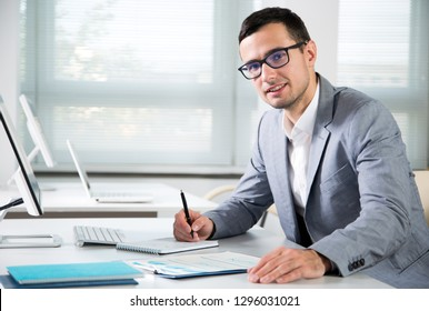 Portrait of a young businessman at the workplace in the office