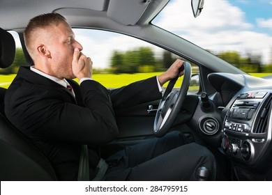 Portrait Of A Young Businessman Yawning While Driving Car