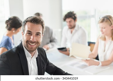 Portrait of a young businessman,he is turned back on his chair at an office business meeting. The team is sitting at a table in a luminous white open space, brainstorming some new ideas.