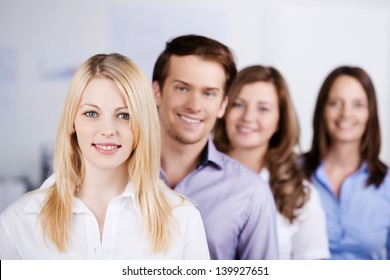 Portrait of young businesspeople standing in a row at office