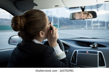 Portrait of young businesswoman applying mascara in car
