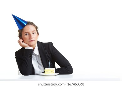 Portrait of young businesswoman in birthday cap with piece of cake on saucer in front