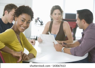 Portrait of young businesswoman with colleagues discussing in conference room