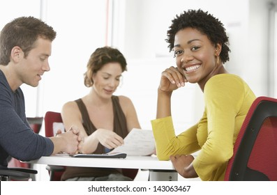 Portrait of young businesswoman with colleagues in meeting room